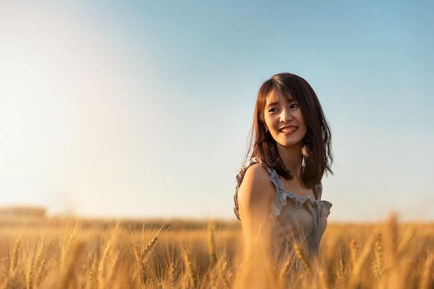Красивая и счастливая азиатская женщина наслаждаясь жизнью в поле ячменя на заходе солнца.