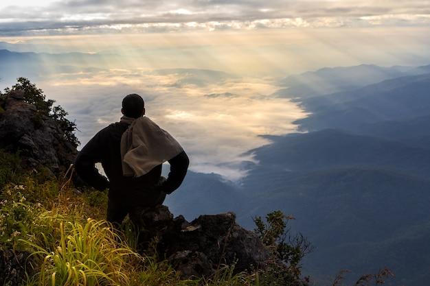 山の頂上にいる旅行者、彼は日の出を見ている岩の上に座っている