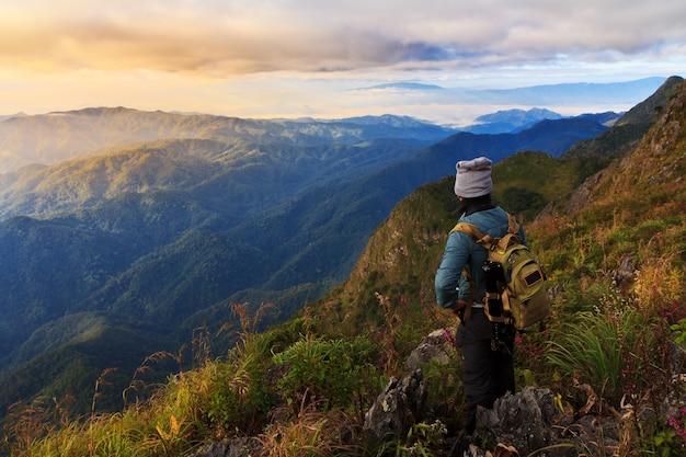 山の頂上にいる旅行者、彼は日の出を見ている岩の上に立っている