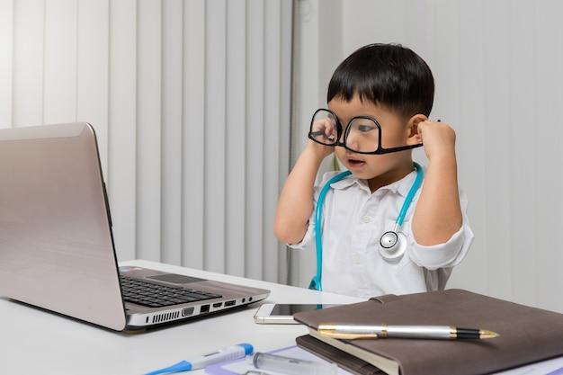 医者の制服の小さな男の子が眼鏡を間違って着ている