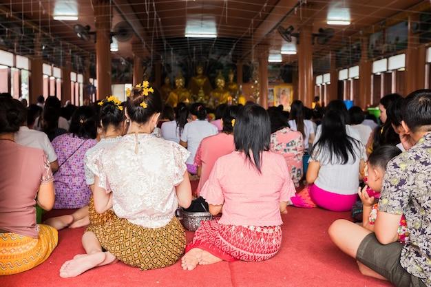 寺院の説教を聞いて座って、ネイティブの服を着た仏教徒