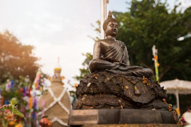 ソンクラーン祭りの寺院で砂の塔の背景を持つ仏像