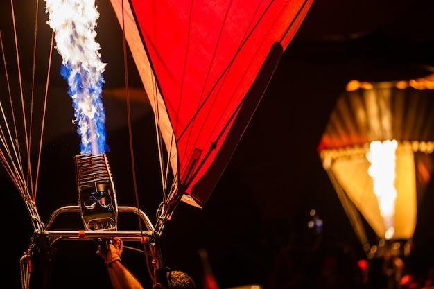 Горелки на горячем воздушном шаре загораются, посылая вспыхнувший газ на воздушных шарах в праздничную ночь