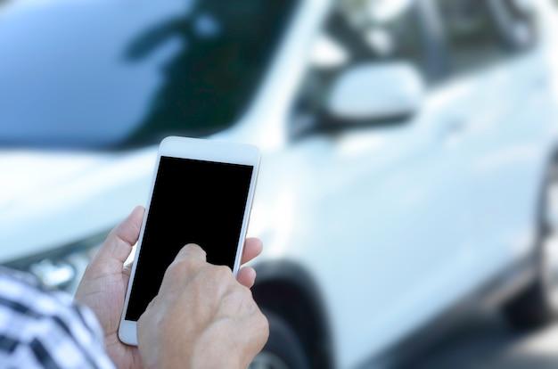 女性は都市の道路上の携帯電話を使用します。