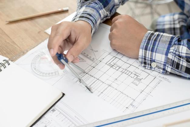 青写真に取り組んでいる建築家。オフィスで鉛筆で青写真と建築モデルに取り組んでいるカジュアルな男。