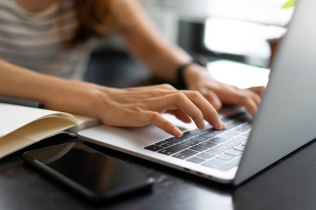 アジアビジネスの女の子がカフェでラップトップコンピューターでの作業を開始