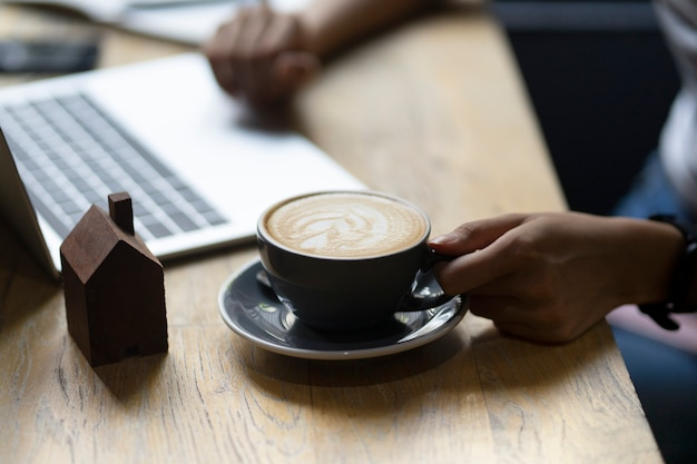 ホットコーヒーカップを保持していると木製のテーブルにラップトップコンピューターでウォーキングビジネス手