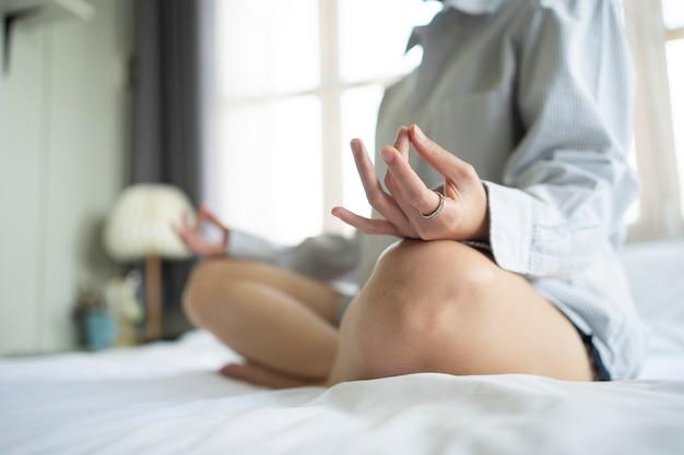 女性はベッドで瞑想を実践