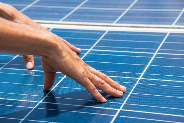 Рука на панели солнечных батарей на солнечной ферме природная энергия - это чистая энергия.
