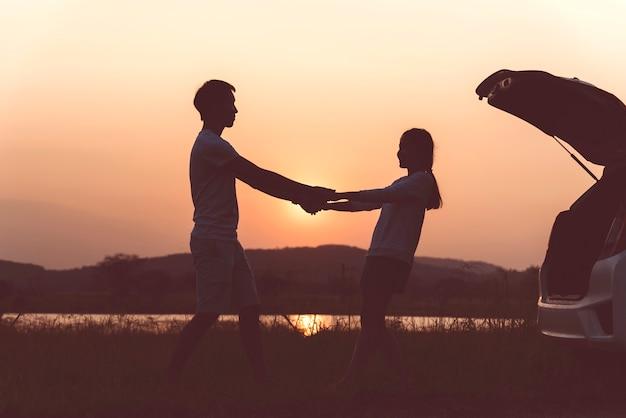 ロマンチックなシルエットカップルの恋人は、夕日のビーチで魅力的です