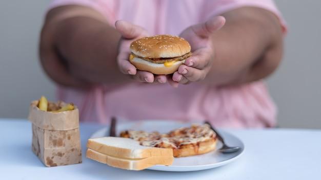 肥満の女性がジャンクフードを食べる