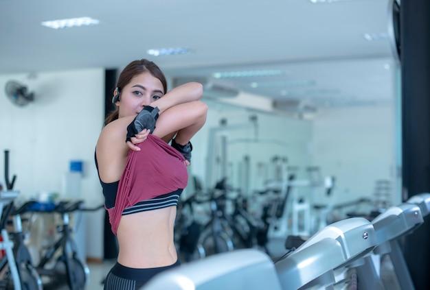 ジムでトレッドミルマシンで実行して運動フィットネス女性のスライドビュー。