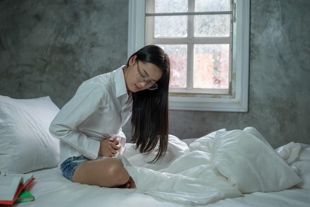 Молодая женщина страдает от боли в животе, сидя на кровати у себя дома