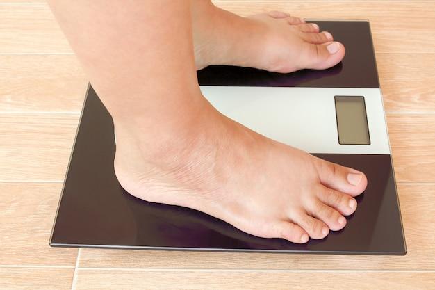 体重計の上に立って太った女性の足のクローズアップ。
