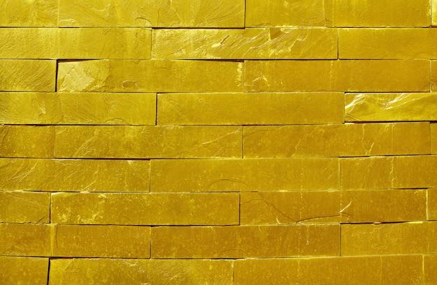背景の高解像度で自然な表面の黄金のスレートの石の壁のテクスチャ
