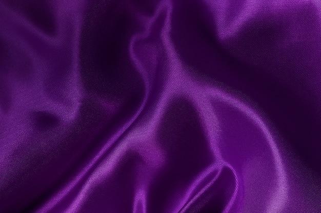 紫の布の布のテクスチャとデザインアート作品、シルクやリネンの美しいしわくちゃのパターン。