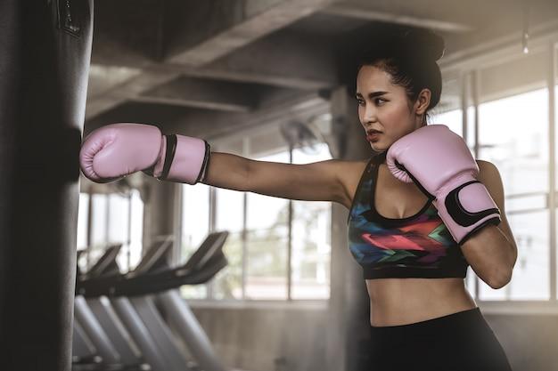 Красивые азиатские женщины пробивают мешки с песком в спортзале