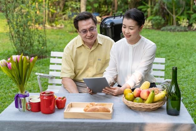 Пожилая пара сидит и смотрит на экран планшета