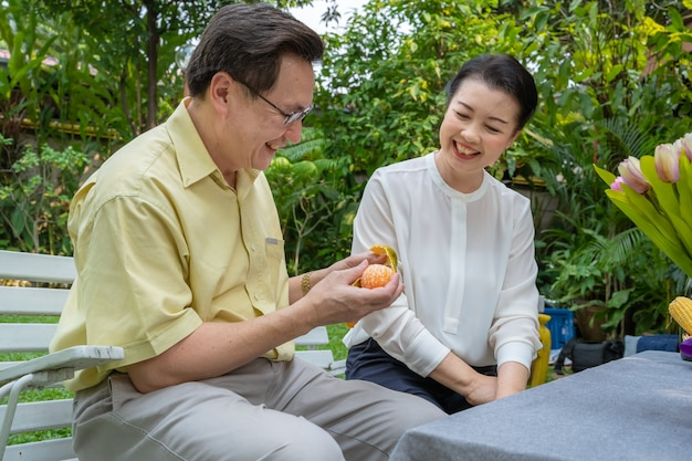 アジアの老夫婦はオレンジを食べて食べることでお互いの世話をしています。家族の概念、カップルの概念