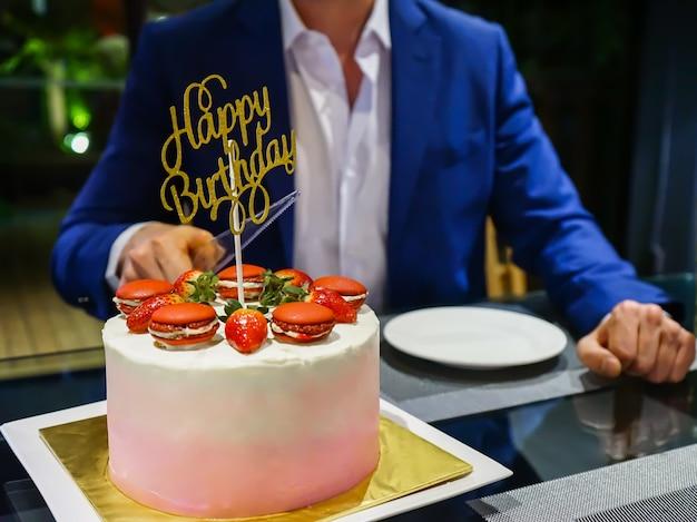 紺の男が誕生日のケーキを切る準備をする