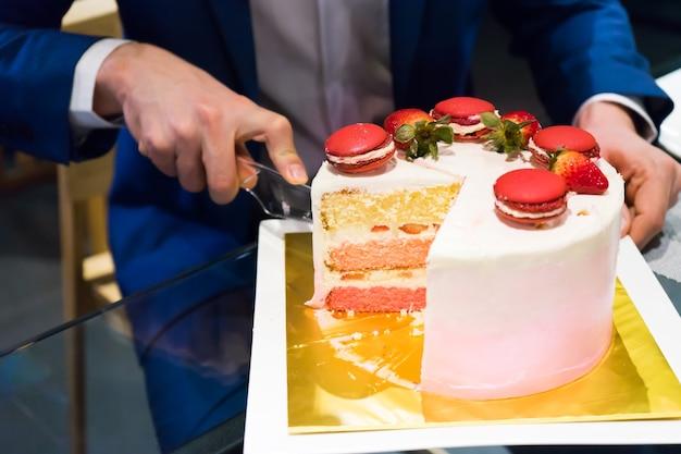 淡色のパブで誕生日ケーキをカットしている紺色の男