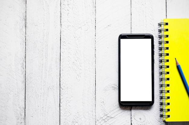 白い木製のボードに置かれた空のスクリーンを備えたスマートフォン。