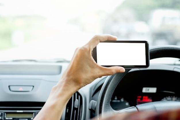 男性の手は車でスマートフォンを使用しています。