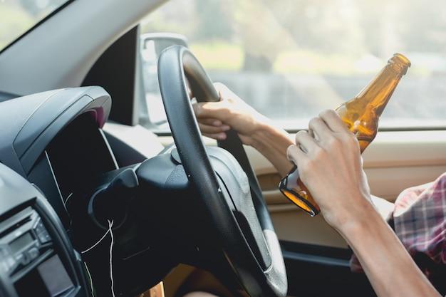 若い観光客がアルコールを飲みながら運転しています。