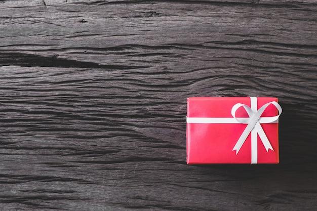 Красная подарочная коробка на старый деревянный пол.