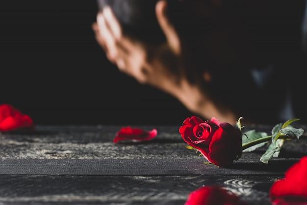 強調している男性と黒いテーブルの上に赤いバラ。