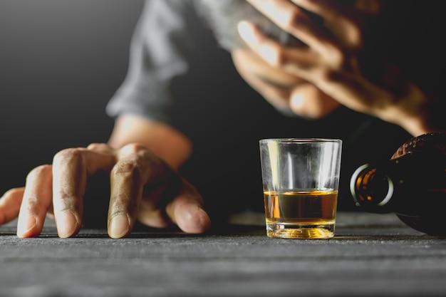 小さなガラスのアルコールを黒いテーブルの上に置きます。