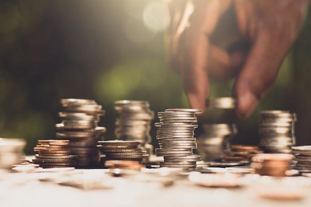 Многочисленные монеты были сложены, руки человека поднимали монеты, когда светило утреннее солнце.