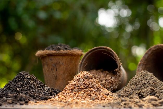 土壌、肥料、おがくずが緑の自然の真ん中に積み上げられています。