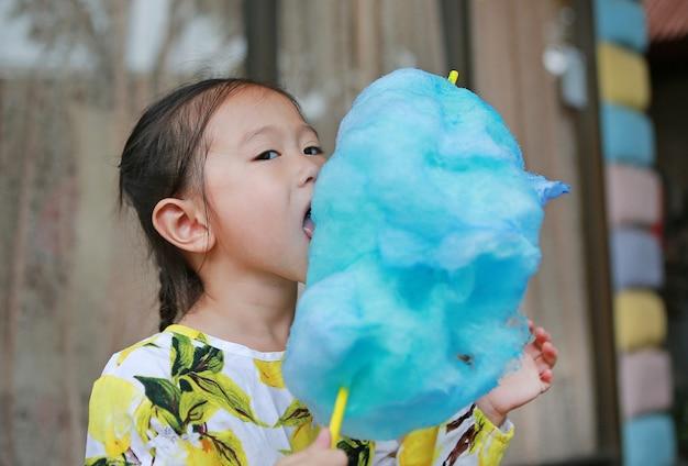 甘いスポンジキャンディーを食べる小さなアジアの子供の女の子