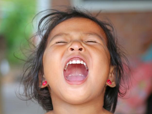 美しい歯で笑ってアジアの子供の女の子を閉じます。