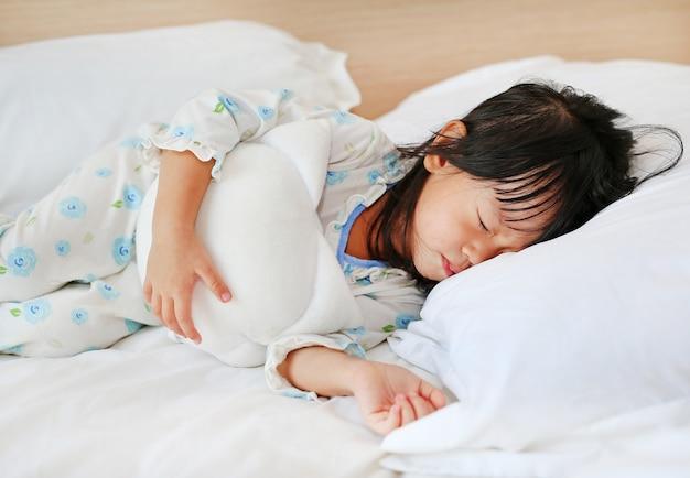 彼女のおもちゃでベッドで寝ている愛らしい少女