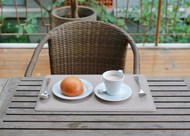レストランでの木製テーブルにパンが入ったカップでホットチョコレートドリンク