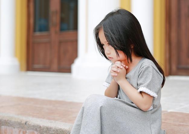小さなアジア人の女の子が座って、教会で祈っている