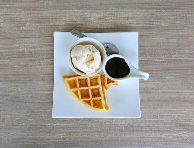 Вафли с мороженым и шоколадом в белой тарелке с деревянным столом