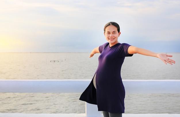 美しい妊娠中の女性は、オープンアームで海岸に立っている。
