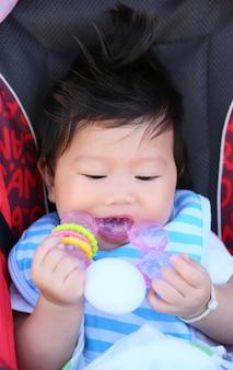 幼児の赤ん坊はおもちゃをかむ。