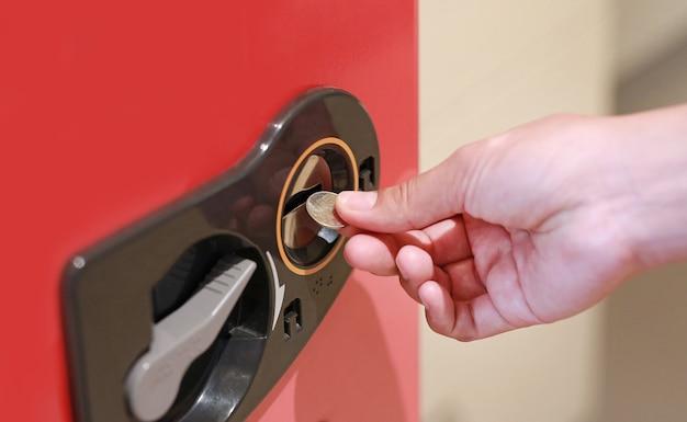 自動販売機にコインを挿入する手。
