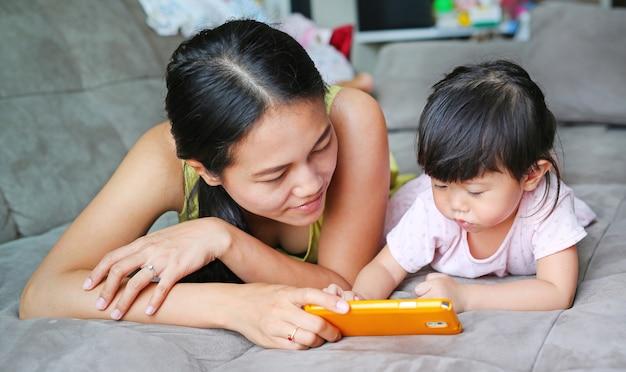 母とかわいいアジアの赤ちゃんの女の子スマートフォンを再生し、敷設
