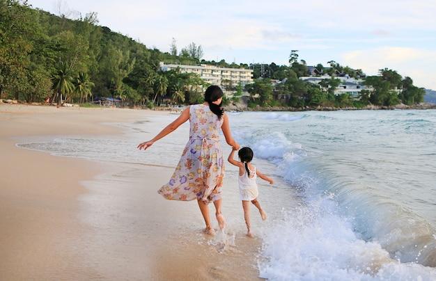 後ろの眺め母と娘はビーチで走っています。