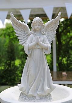 庭で祈っている翼のある天使のアンティークの彫像
