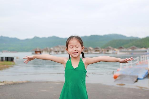 閉じた目小さなアジアの子供の女の子ストレッチアームと丘の中でリラックス。