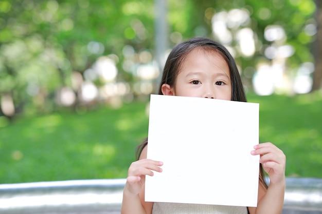 愛らしい小さなアジアの子供の女の子が空白の白い紙を持っています。