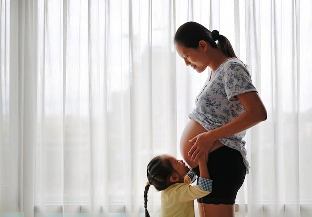 Беременная женщина азии, стоя у окна дома с дочерью, целуя ее животик.