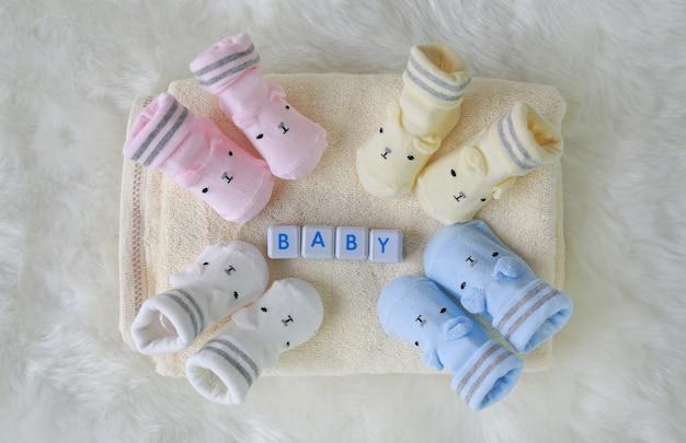 白い毛皮の背景に新生児のための靴下のコレクション。