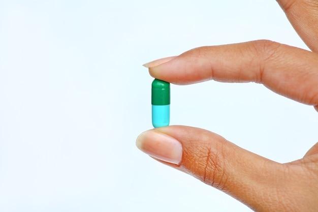 Палец держит таблетку на белом фоне
